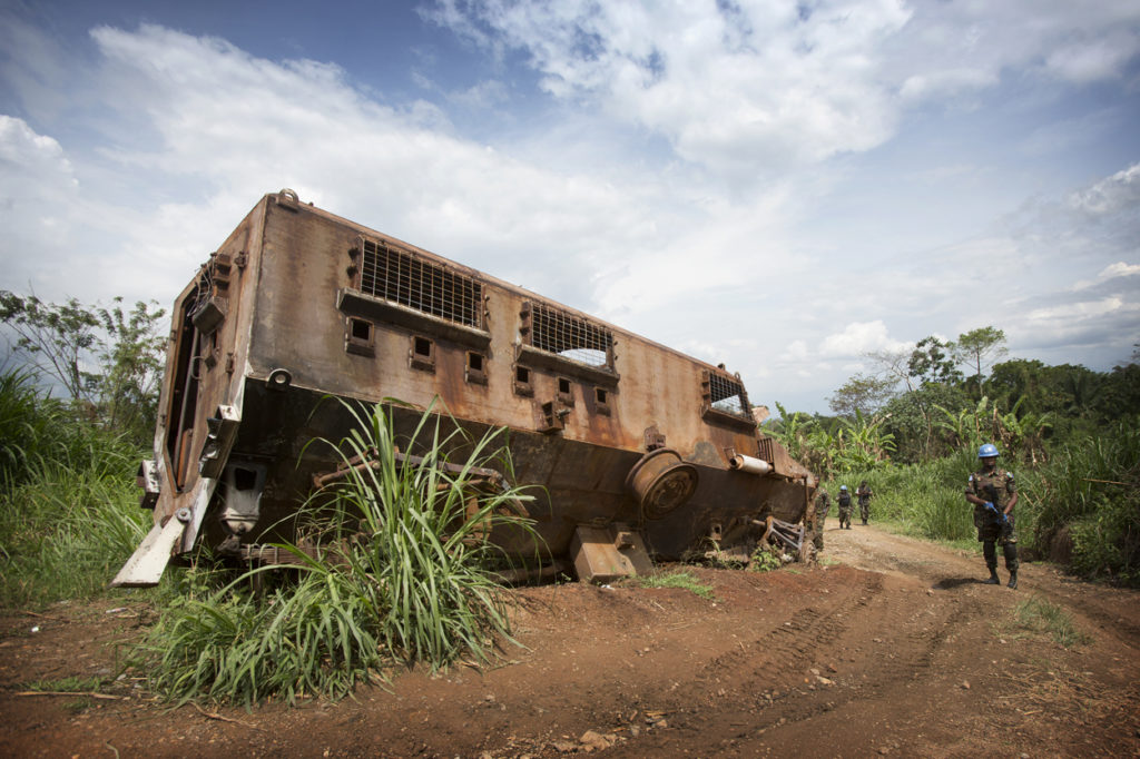 A MONUSCO Peacekeeper stands near the wreckage of a nepalese armored vehicle which was hit the previous year in an ambush from ADF militia in the Beni region, the 13th of March 2014.   © MONUSCO/Sylvain Liechti